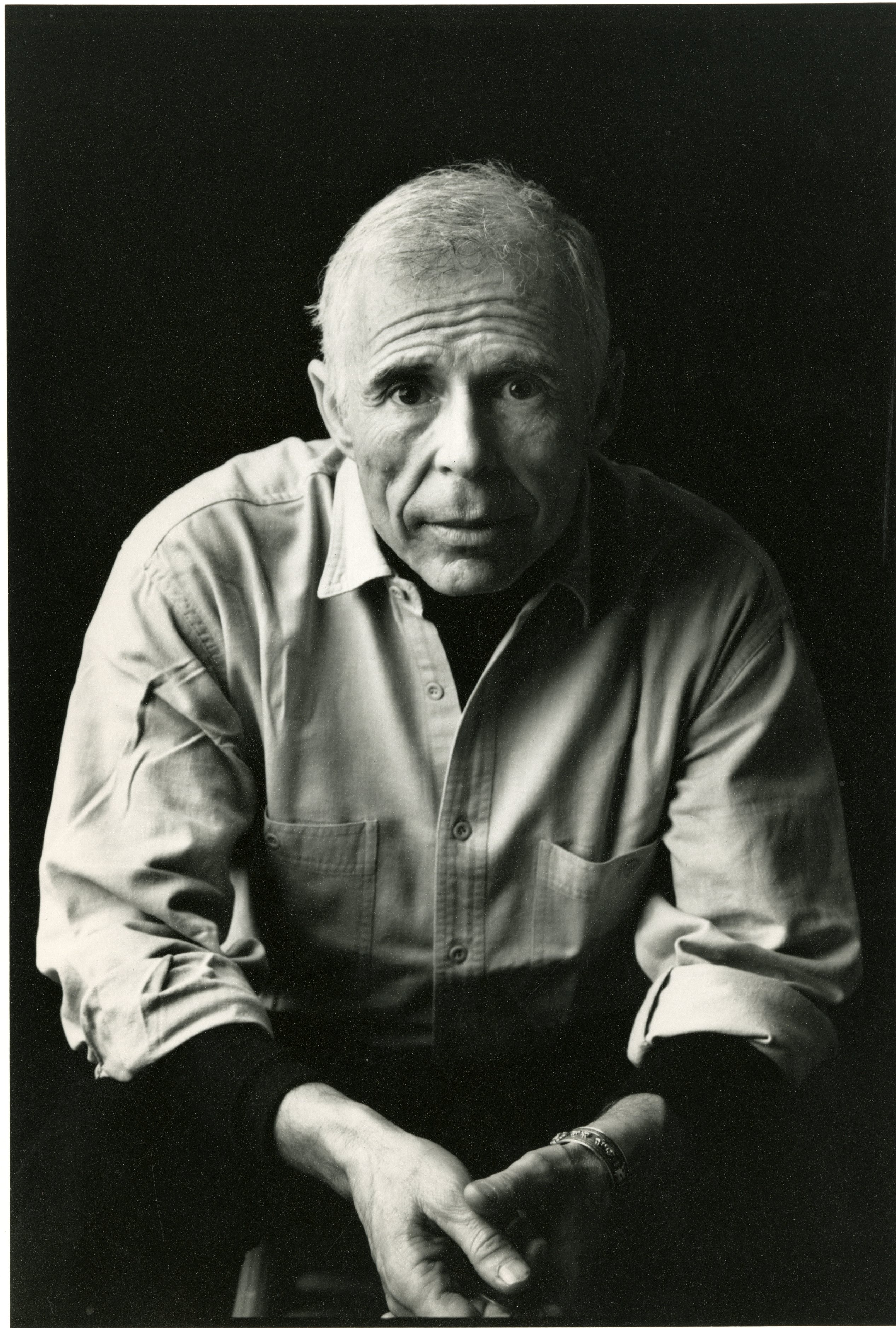 A black-and-white portrait of Jean-Claude van Itallie, a seated older man with white hair wearing a collared shirt