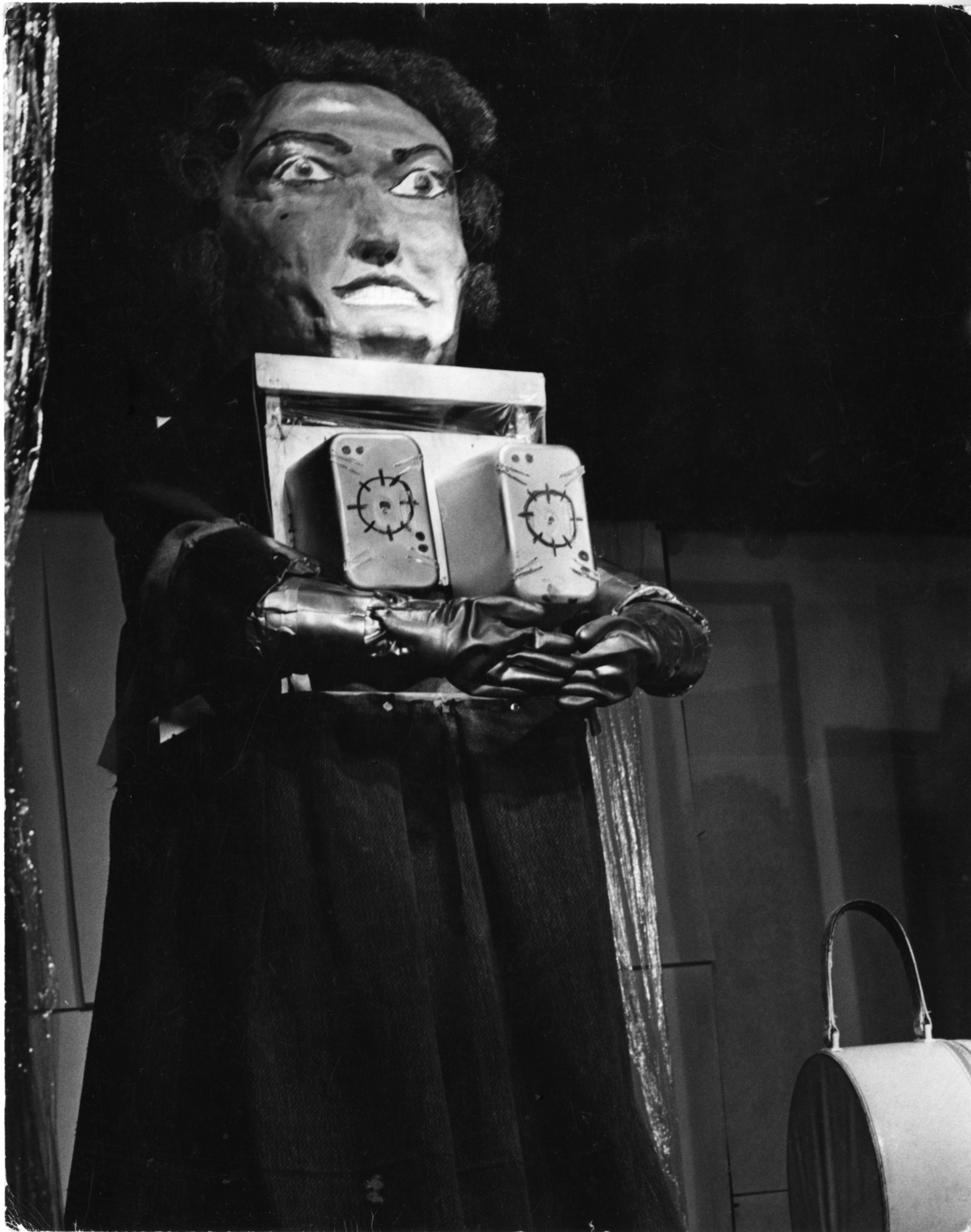 A performer wearing a large mask resembling a human face and wearing gloves, holding a large object