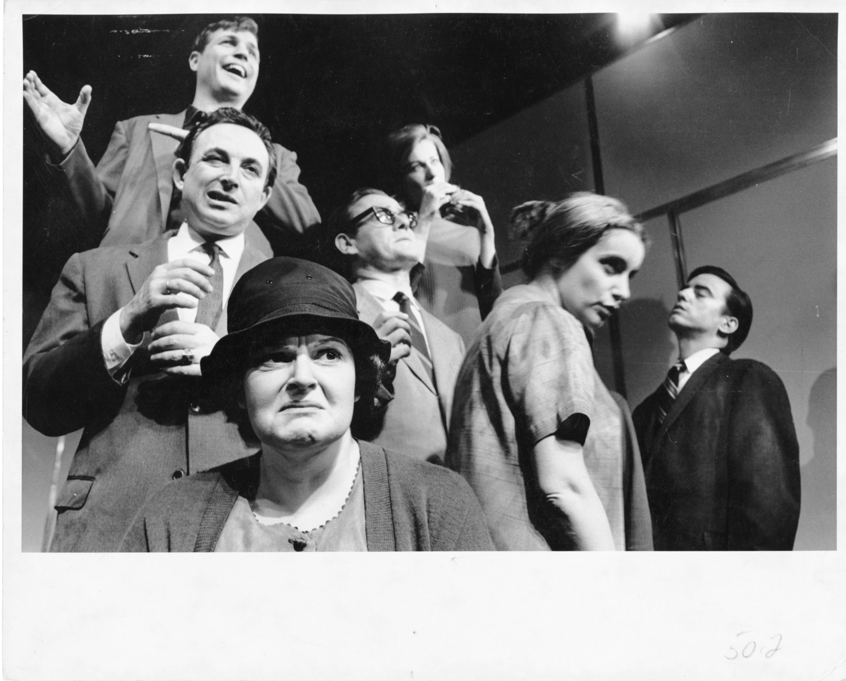 A photo of an ensemble with a frowning woman in a hat in the foreground and four men in suits and two women in the background