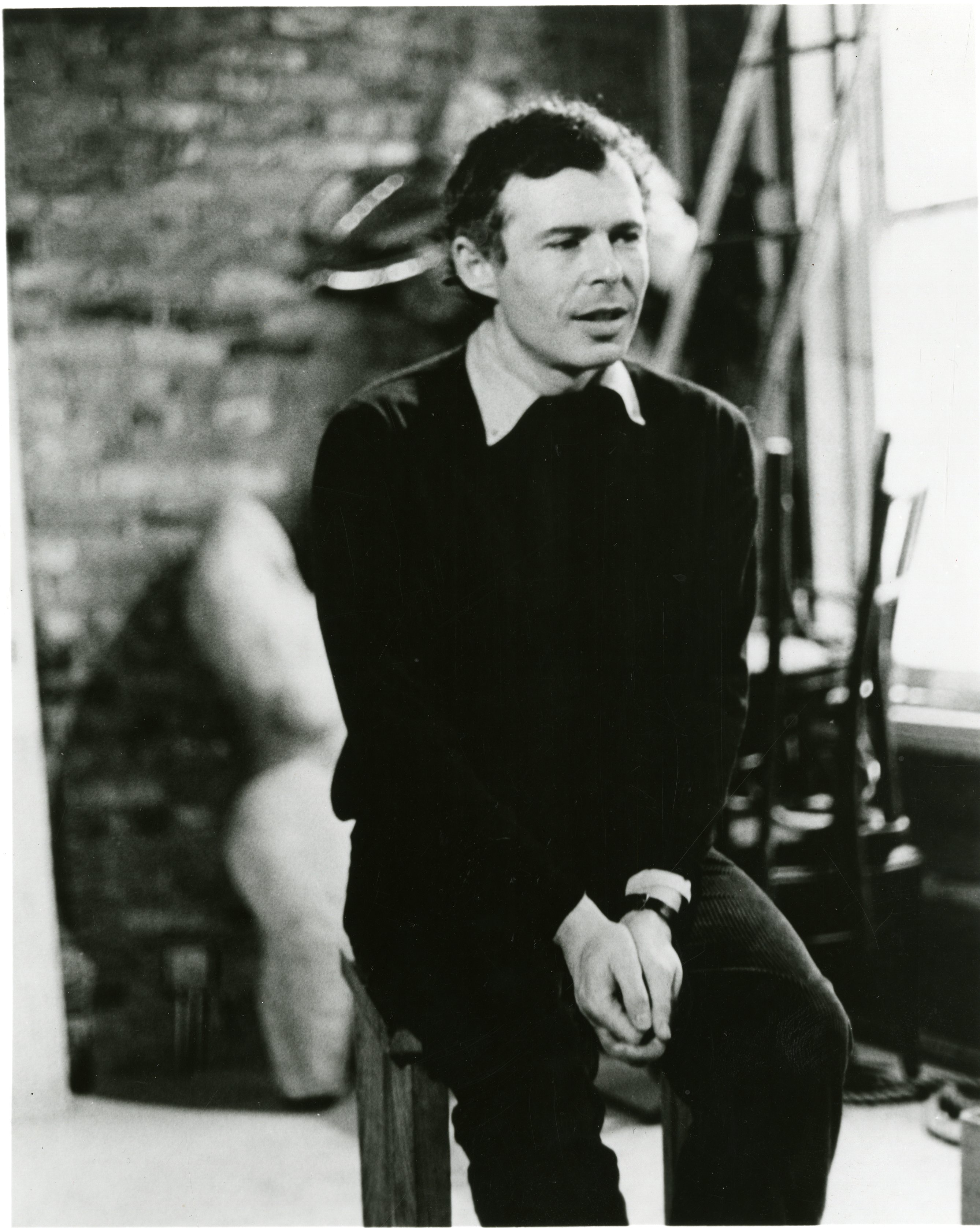 A portrait of Jean-Claude van Itallie as a younger man, seated in a studi with his hands clasped and wearing a collared shirt and sweater