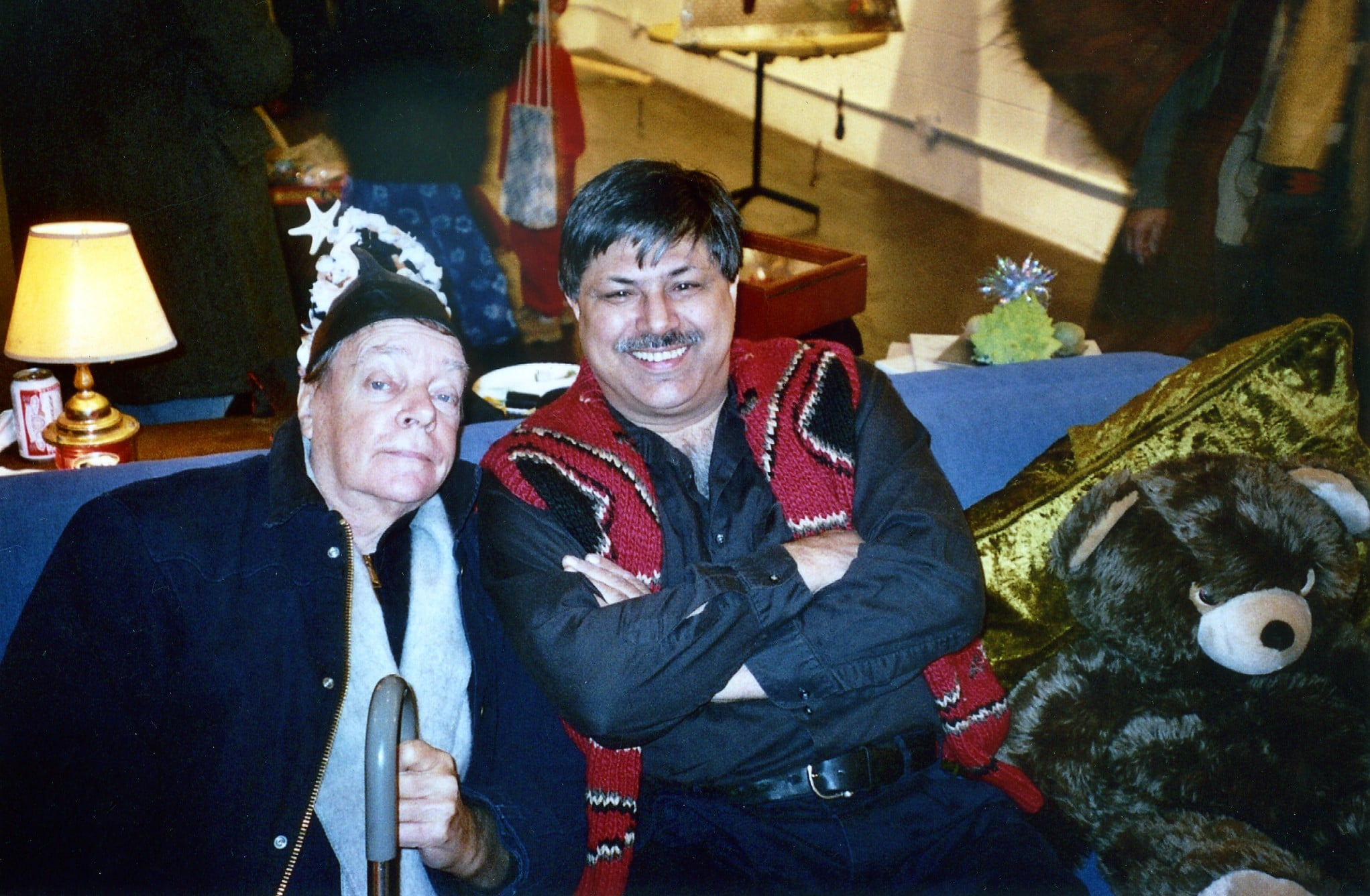 Tom (left) is wearing a hat and blue jacket and holding a cane, and George (right) is smiling with his arms crossed and wearing a black shirt and a red patterned sweater vest.