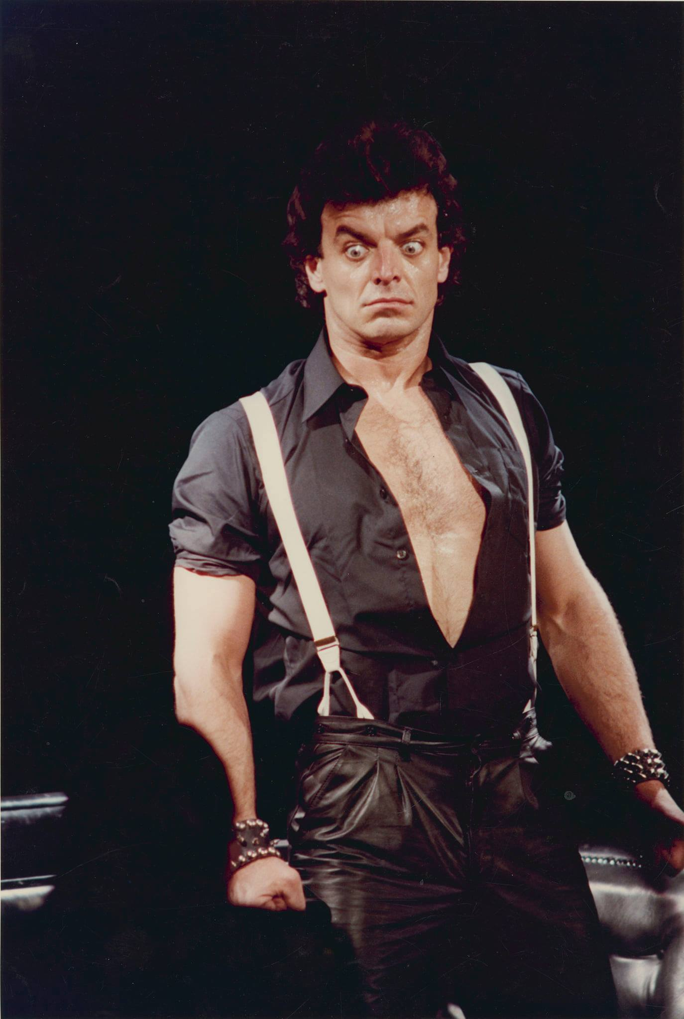 An actor with a shocked expression wearing suspenders and an unbuttoned black collared shirt tucked into leather pants