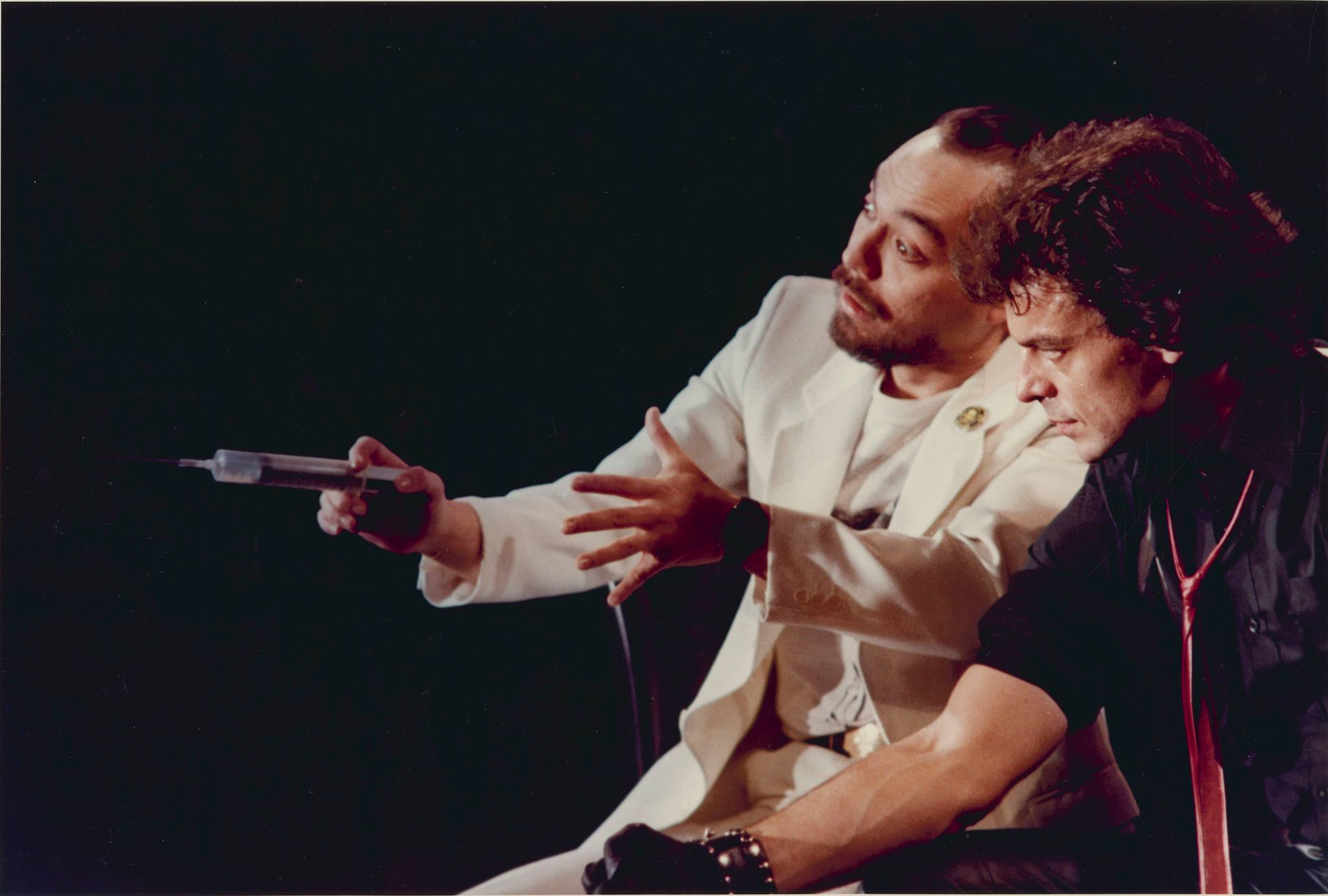 One actor (left) with a beard is wearing a white suit and holding a syringe, another actor (right) wearing a black shirt and red tie is looking at the syringe
