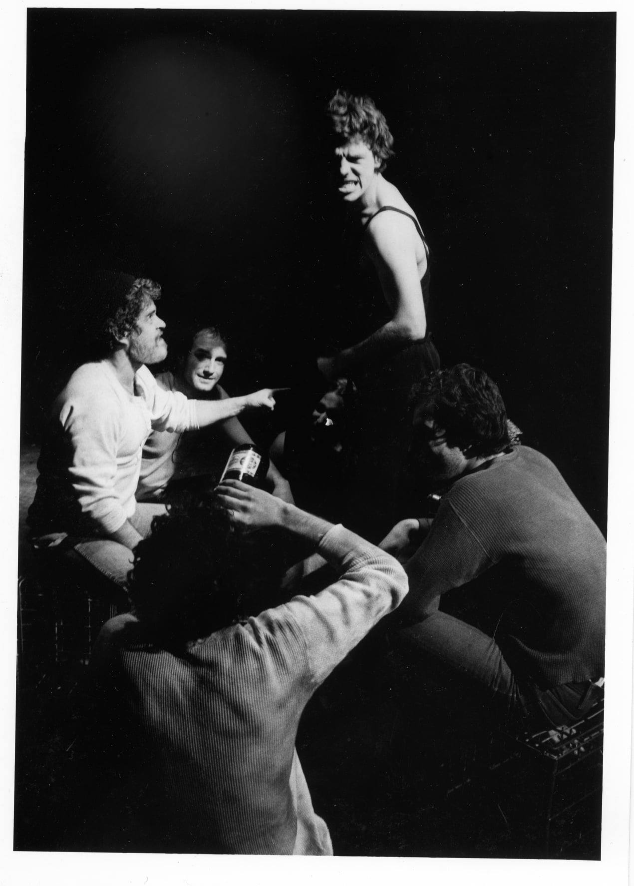 Five actors, one standing with an angry expression and four seated, one is turned away from the camera and drinking from a bottle