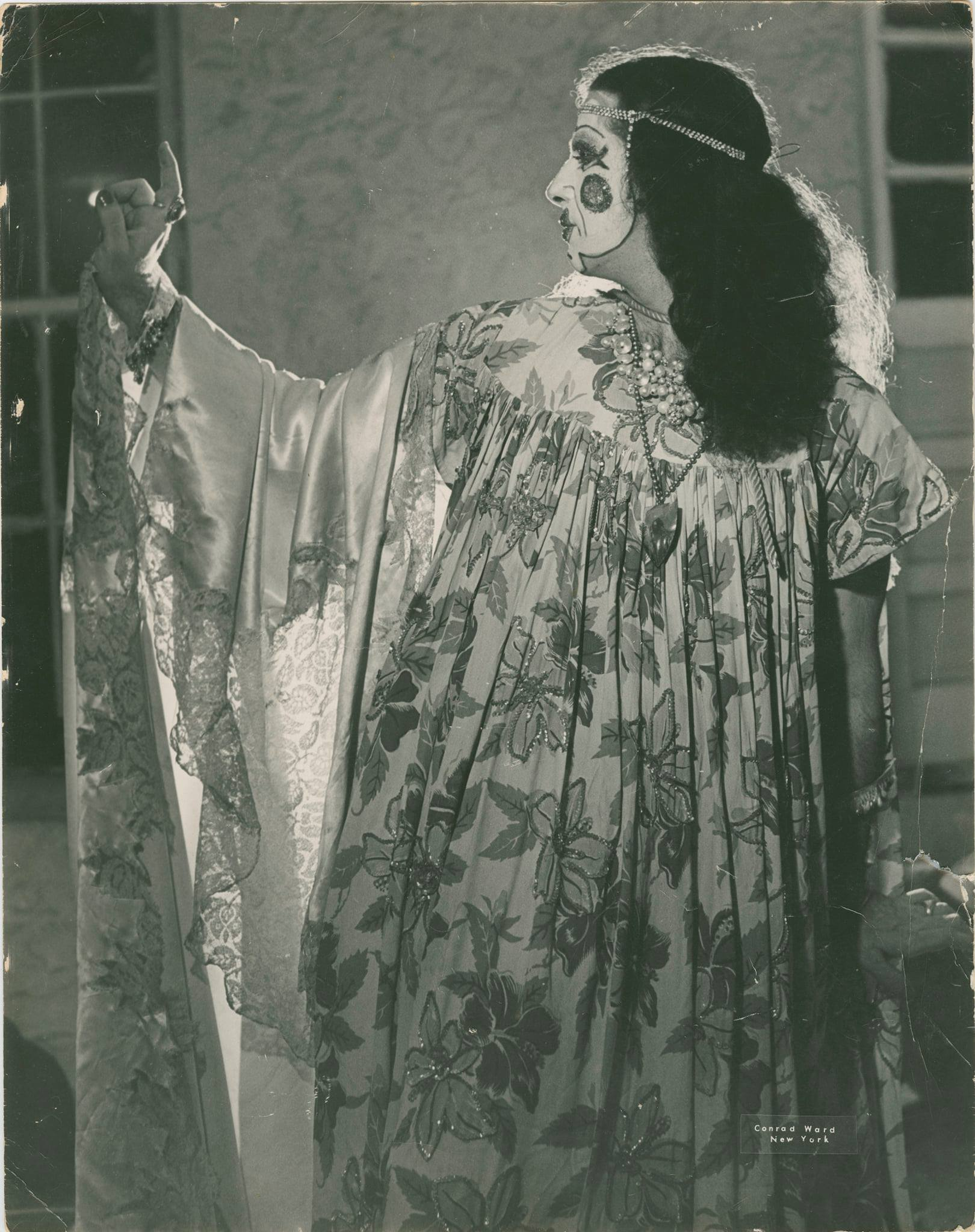 An actor looking to the left (his right) with his finger raised, with his face painted and wearing a long floral and lace costume
