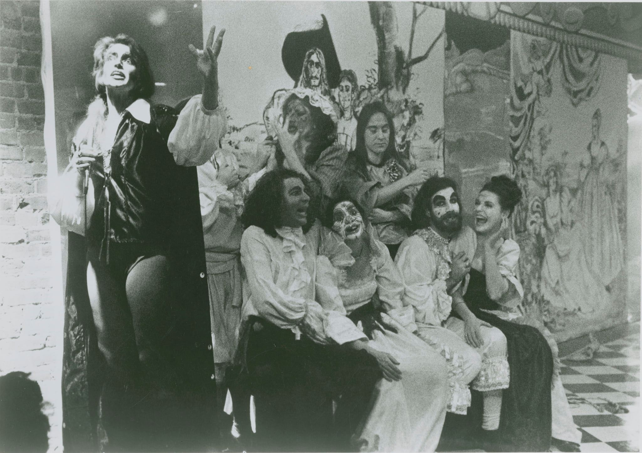 Seven cast members are in front of a mural, four are sitting and three are standing, all are wearing costumes and make-up