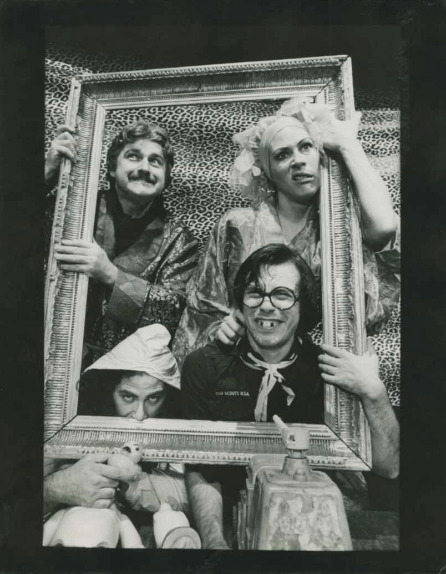 Four actors in costume are holding up a frame in front of a leopard print backdrop