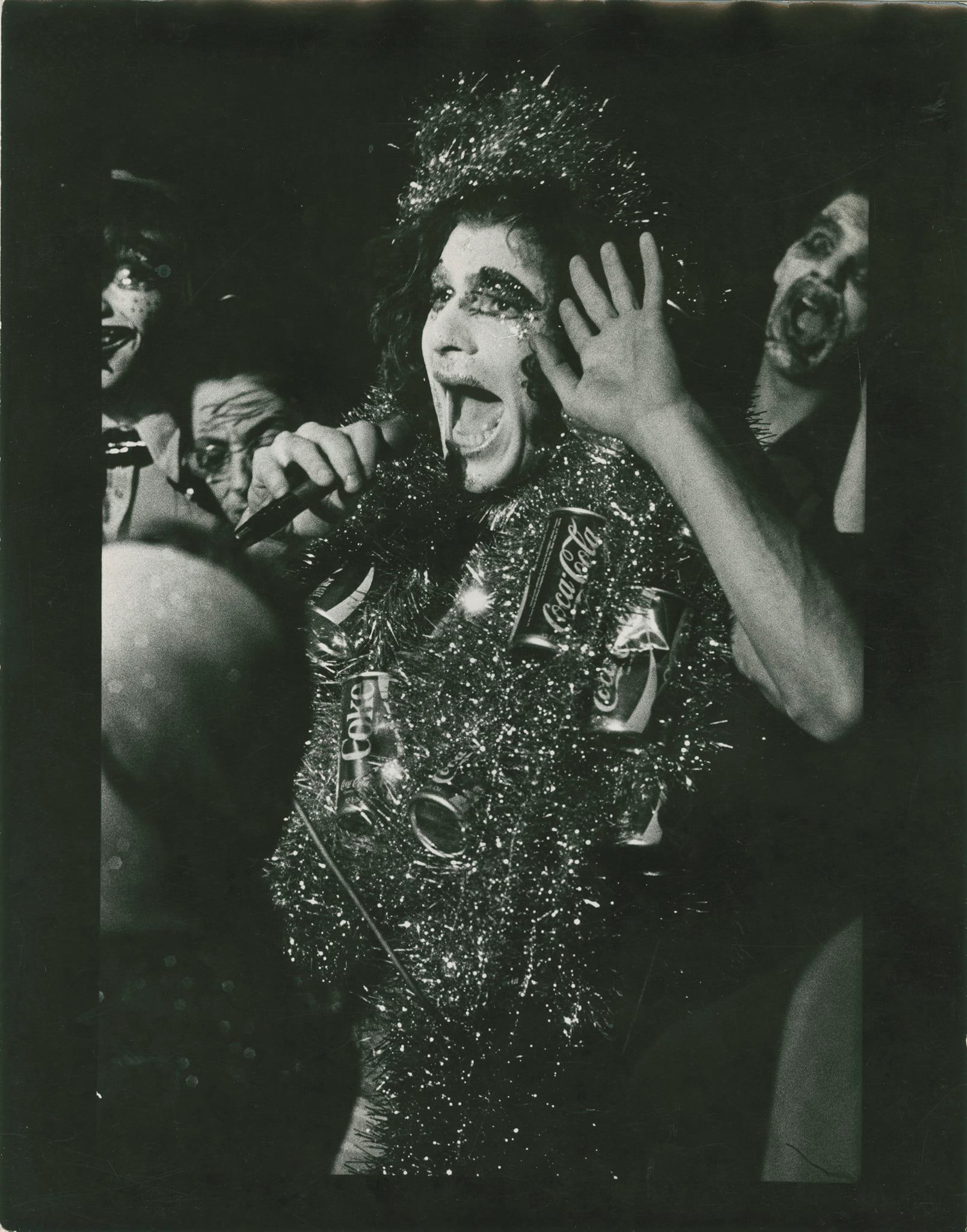 An actor is holding a microphone and wearing a costume made of tinsel and Coca-Cola cans and a crown of tinsel