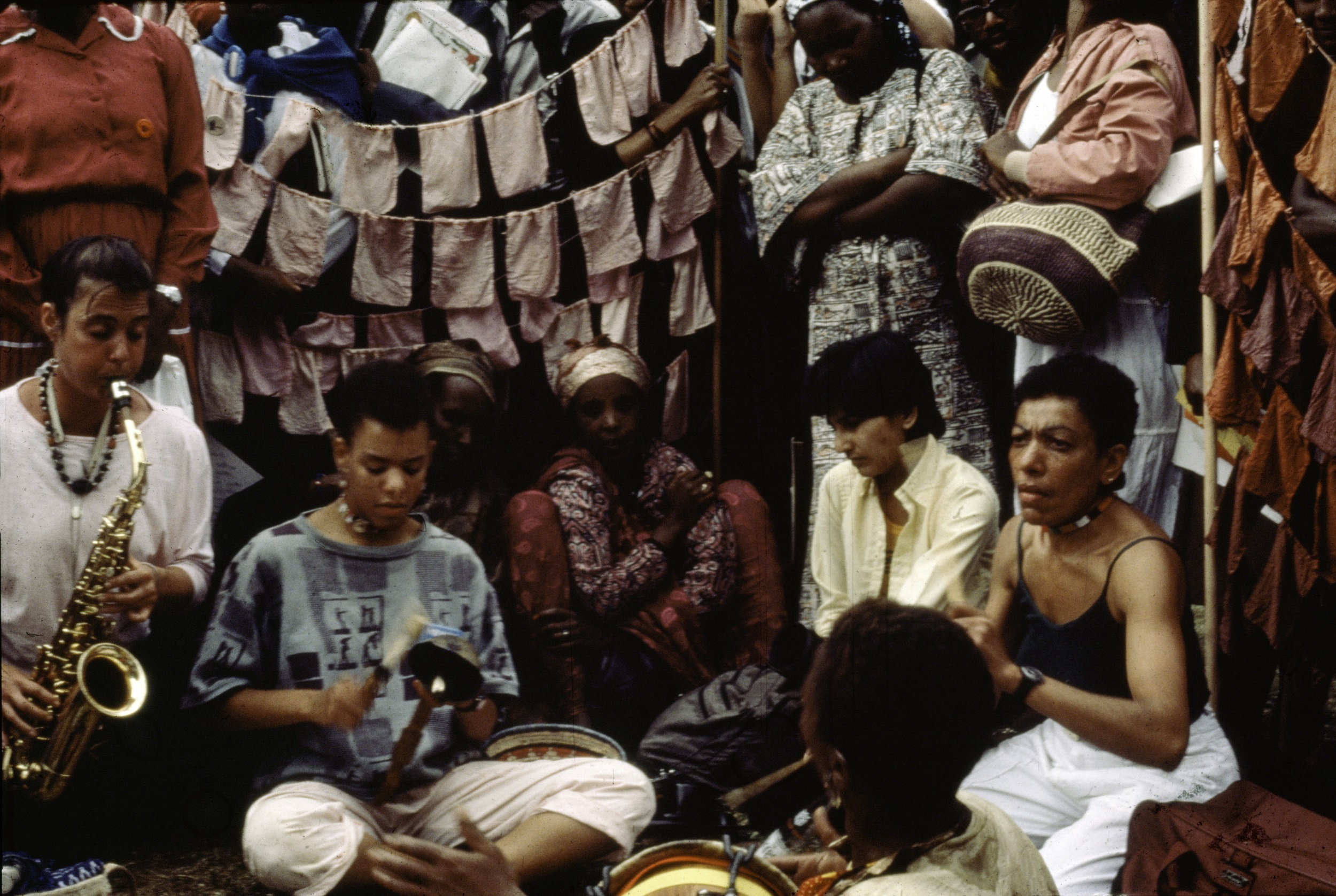 Musicians are seated and playing in front of a backdrop of small cloths hanging on a line.