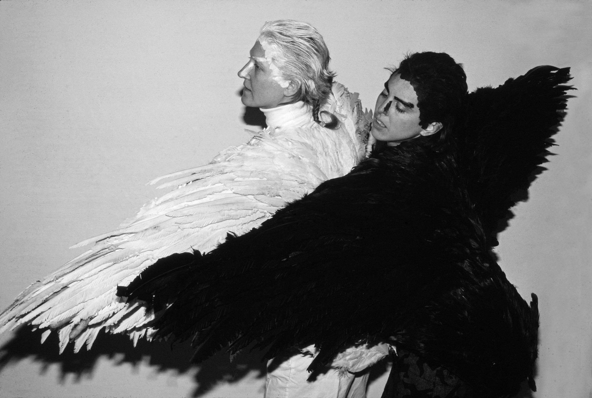 Two performers have their left arms outstretched. The one in the front is wearing a costume made of black feathers and the one in the back is wearing a costume made of white feathers.