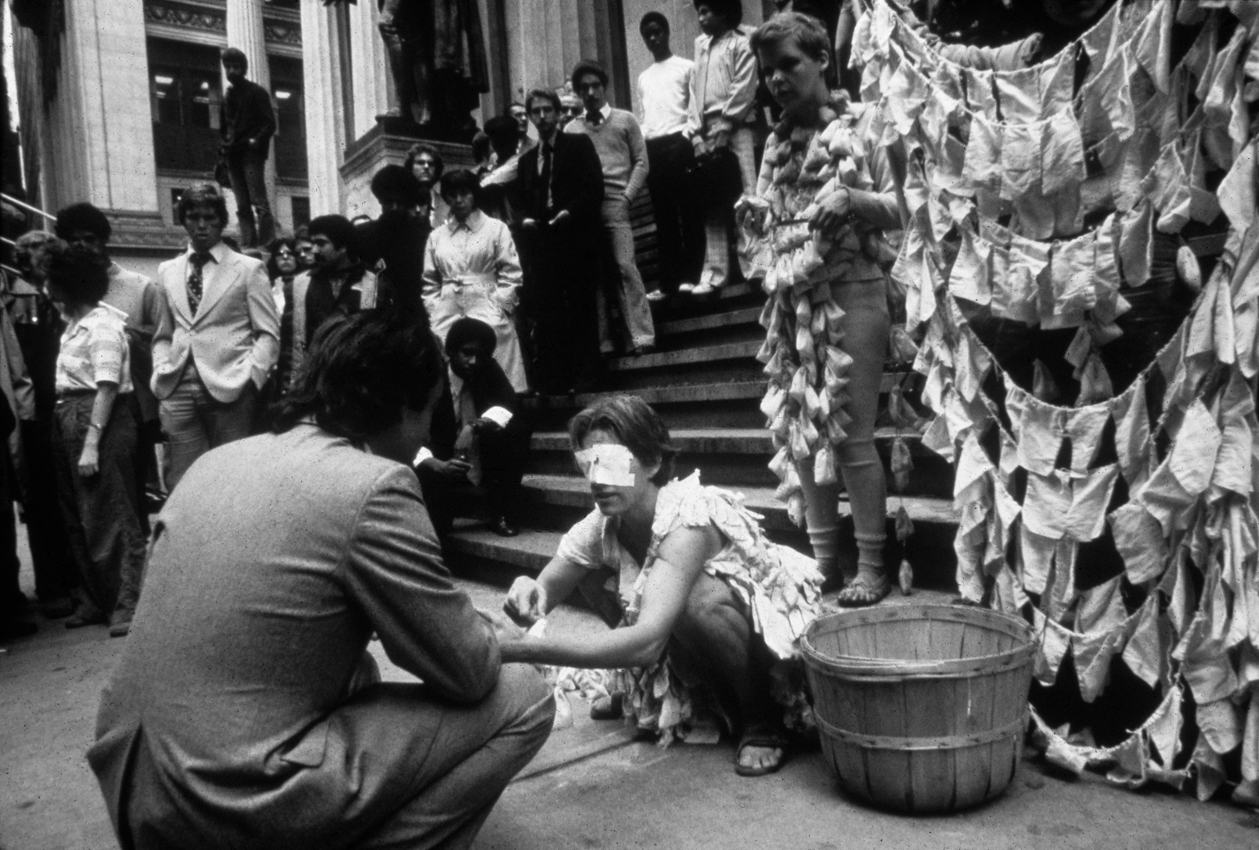 A blindfolded performer is squatting in front of a staircase next to a bucket in front of another performer wearing a costume made of small pouches.