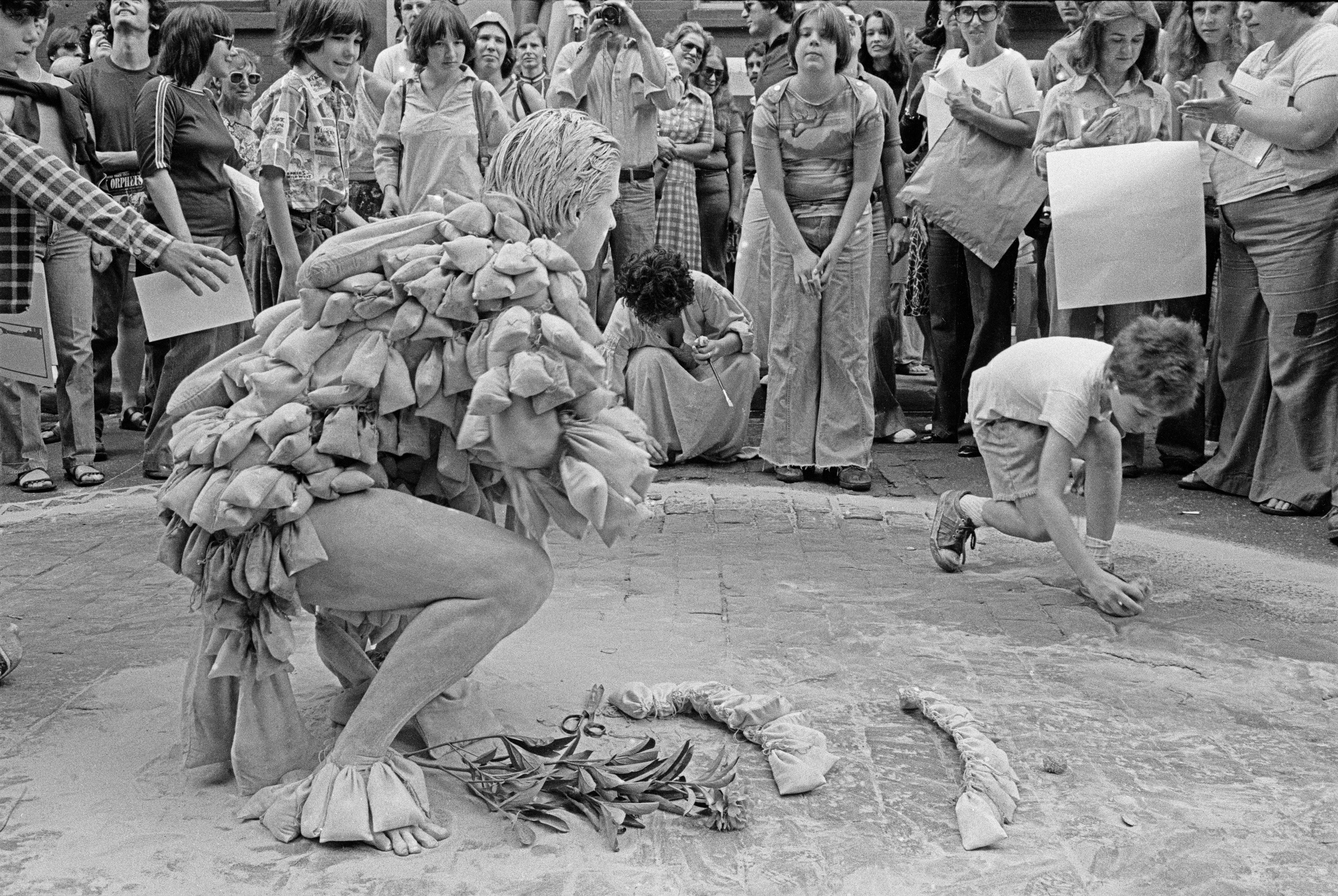 A performer wearing a costume made of lots of small pouches is squatting in the middle of a crowd and looking at a child who is touching the ground