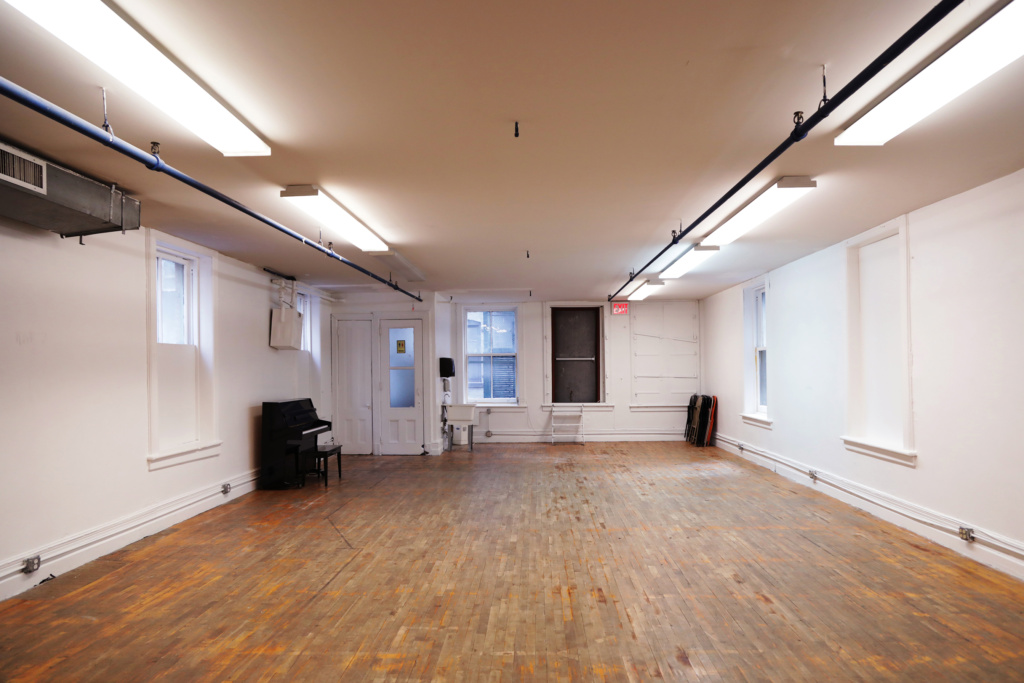 A room with white walls, a white ceiling, and a wooden floor. A piano is in one corner and a stack of folded up chairs is in the other corner. There is a lot of natural light from the windows and artificial light from the ceiling lights.