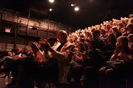 Audience clapping inside La Mama building