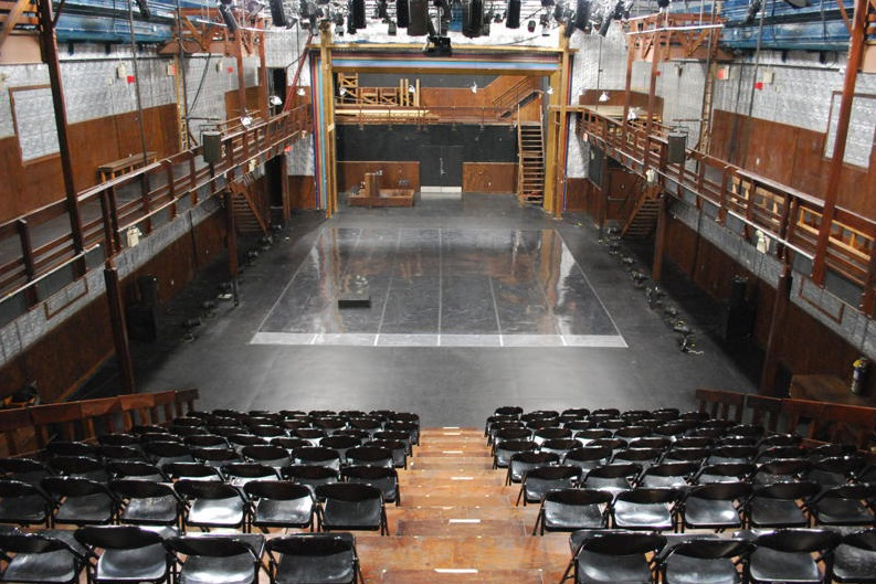 A large performance space with silver tiled walls and a black floor with marley. There is a colorful archway and stairs going up to the balcony. Risers are set up with black folding chairs for the audience. There are theatrical lighting fixtures set up on the ceiling and ladders going up from the balcony area to the ceiling.
