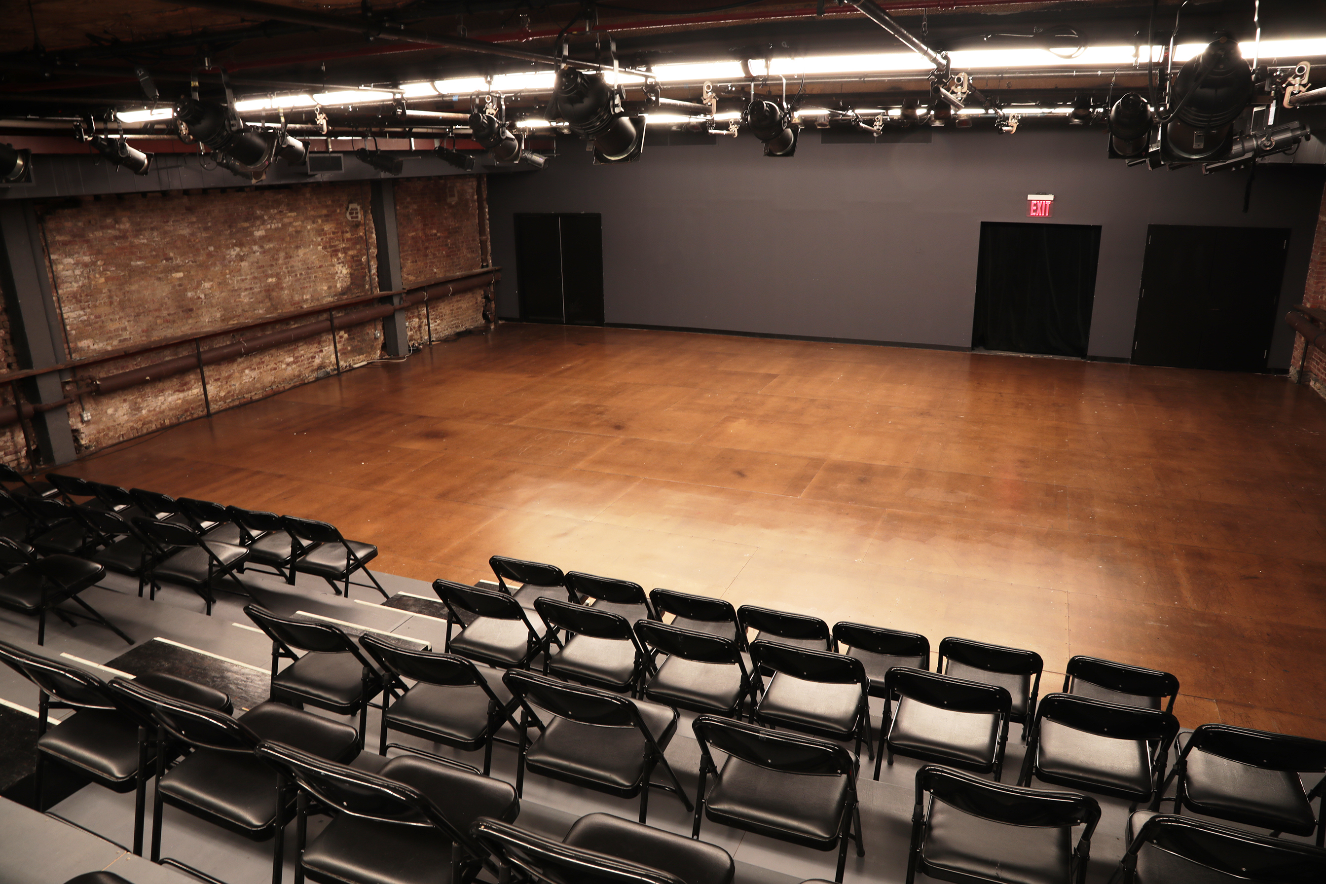 A performance space with one black wall, two brick walls, and a wooden floor. There are risers and black folding chairs set up for the audience. There are theatrical lighting fixtures set up on the ceiling.