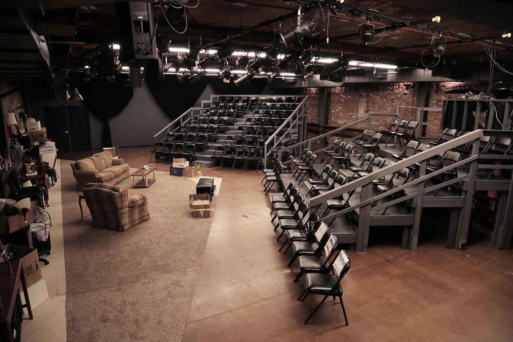 A performance space with one black wall, two brick walls, and a wooden floor. There are risers and black folding chairs set up for the audience. On stage, there is a beige carpet with one couch, an armchair, a table, and cardboard boxes. There are theatrical lighting fixtures set up on the ceiling.