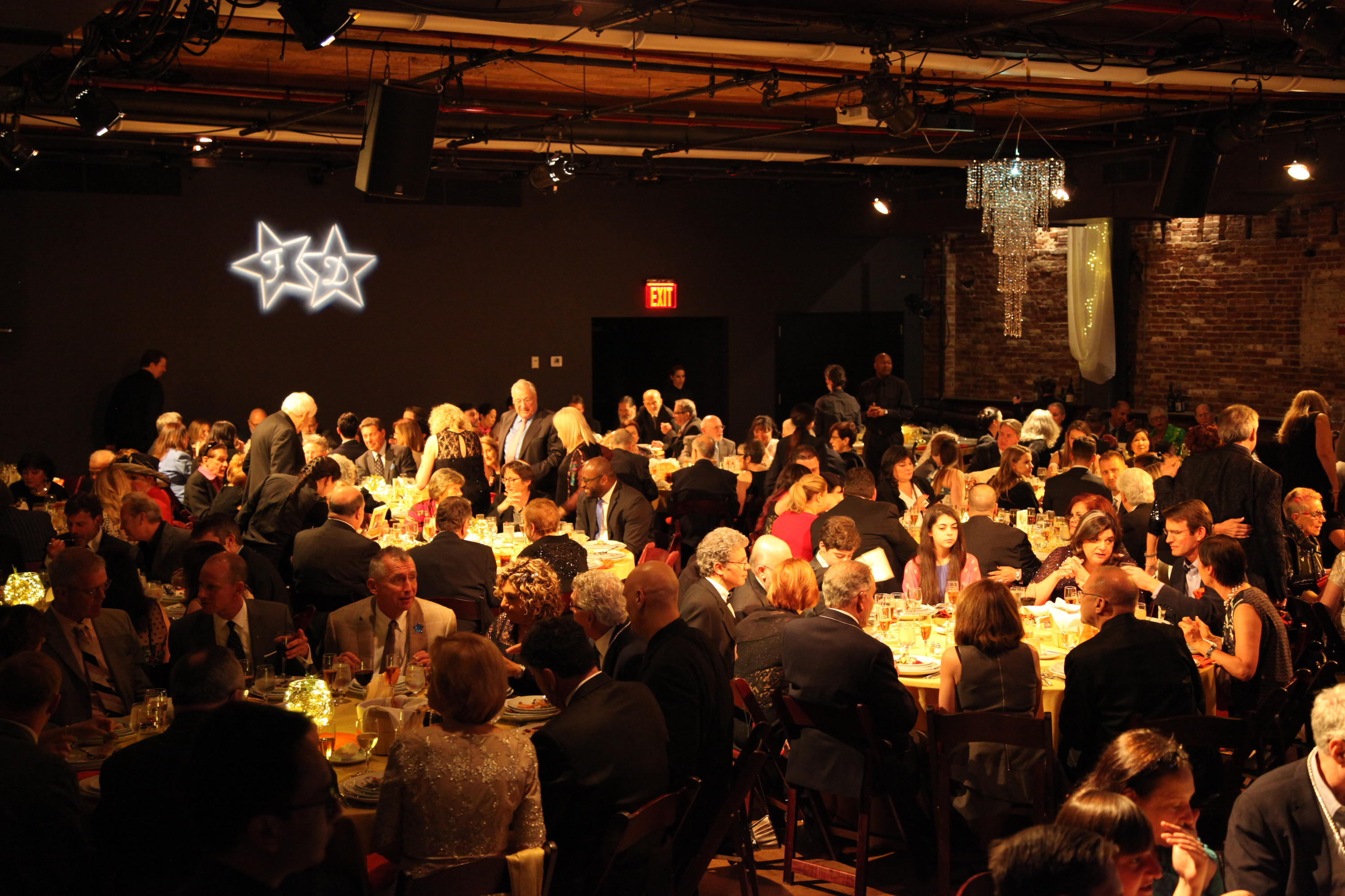 A venue space with one black wall and one brick wall. There are neon lights on one wall, and a chandelier is attached to the ceiling. Several round tables and chairs are set up throughout the room, with formally-dressed people sitting and standing.