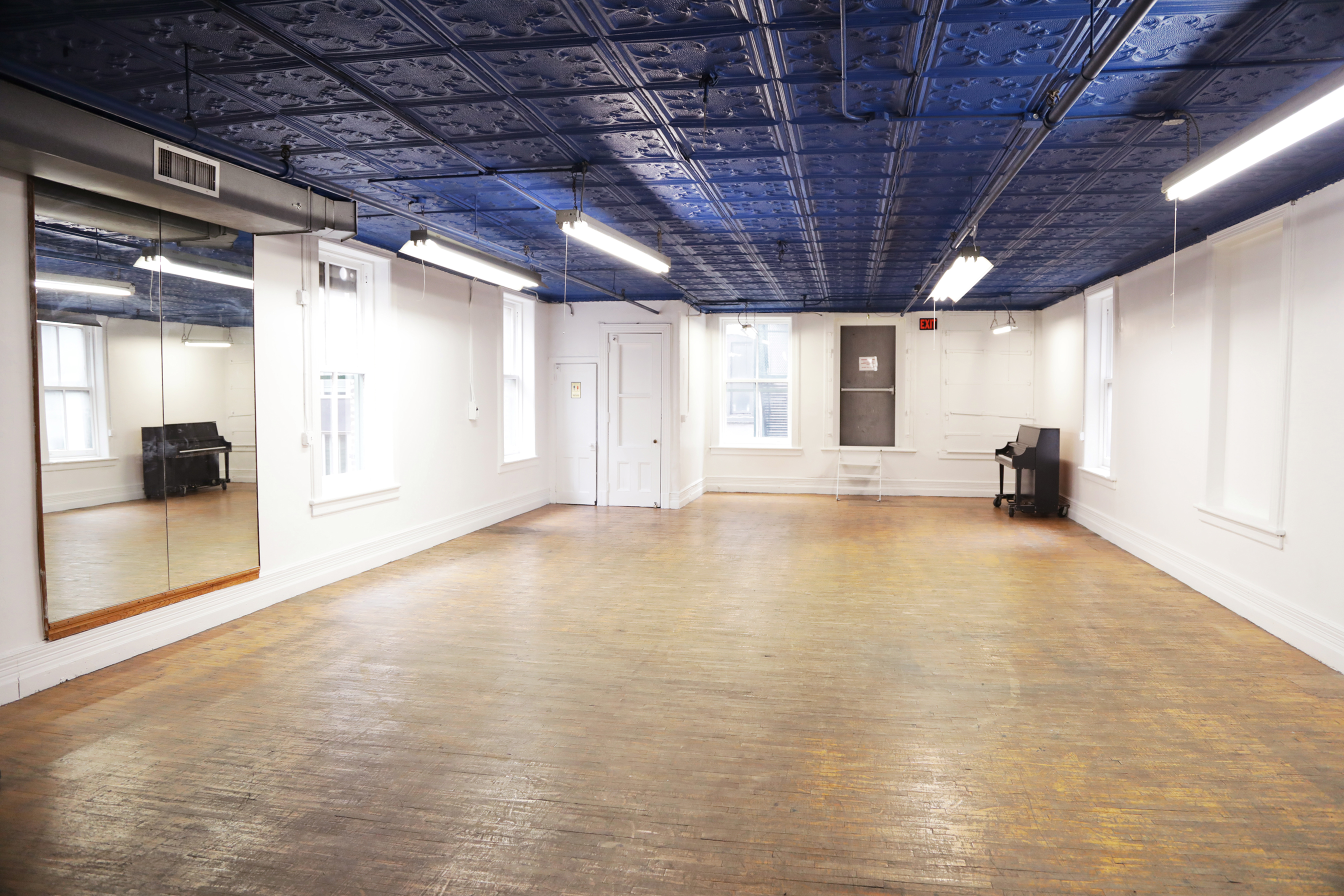 A room with white walls, a blue tiled ceiling, and a wooden floor. A piano is in one corner and on the opposite wall are mirror panels. There is a lot of natural light from the windows and artificial light from the ceiling lights.