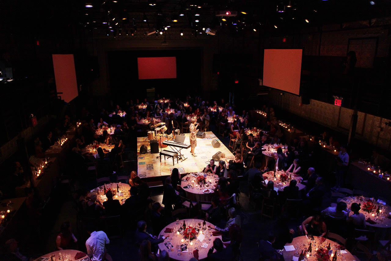A large dimly-lit venue space with several people sitting around round tables and a raised platform in the center with a performer, piano, drums, and other instruments