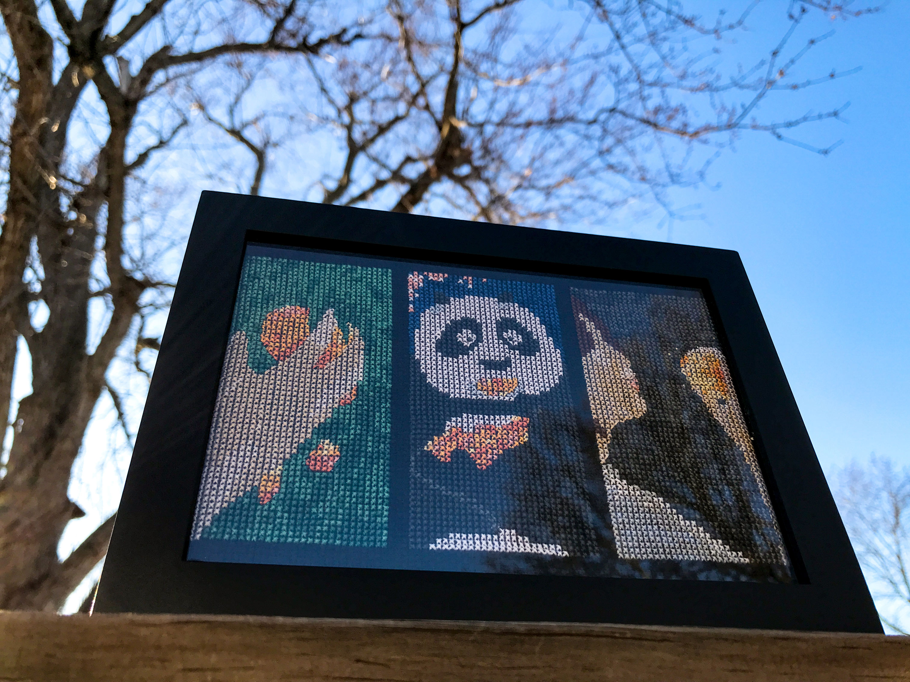 Framed cross stitch depicting three film scenes