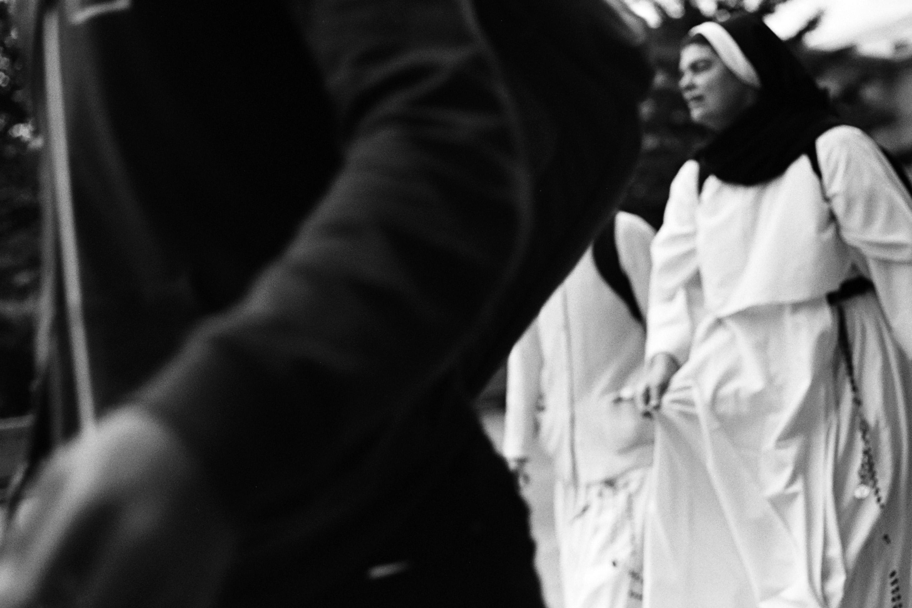 Photograph of a nun walking behind a man