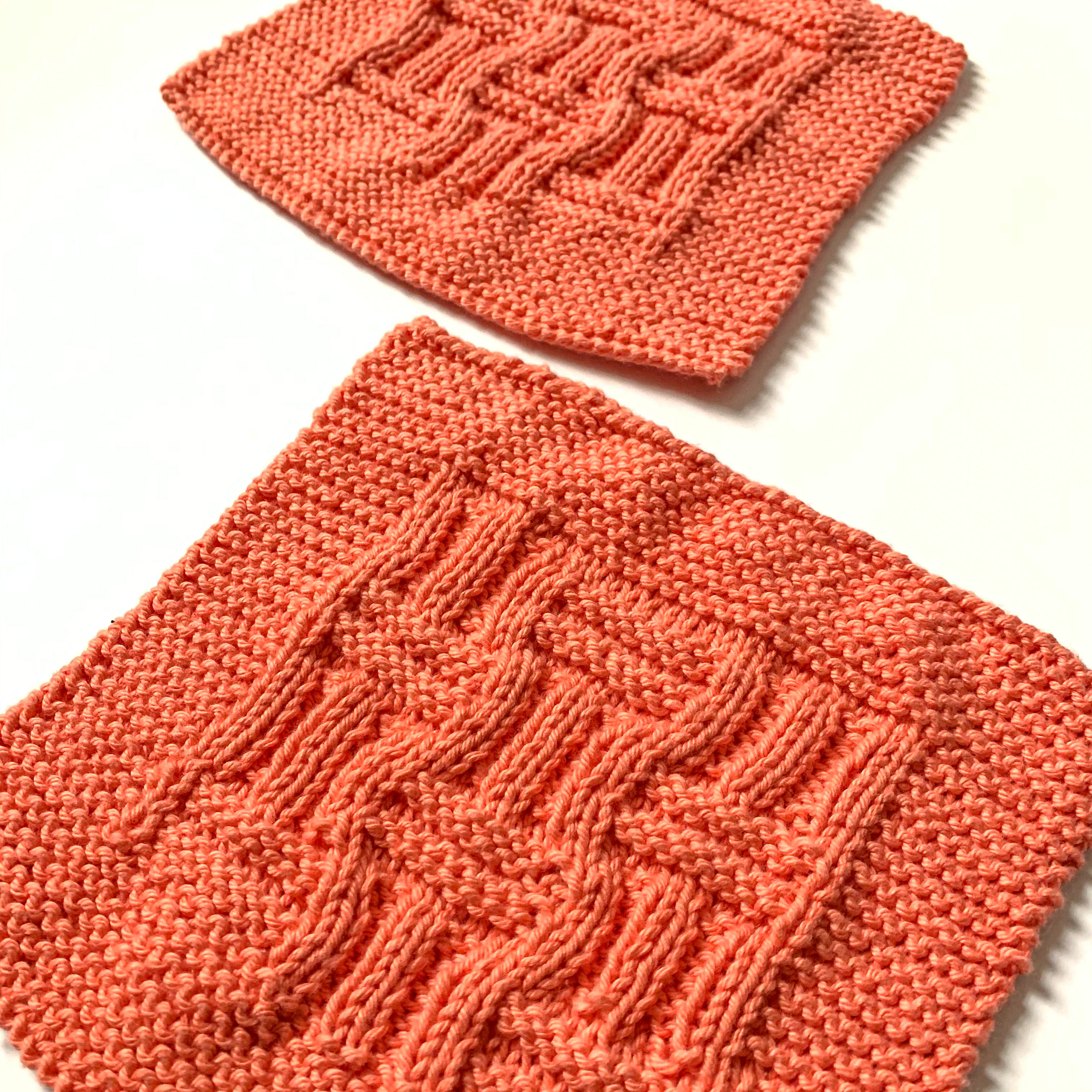 two square salmon knitted cotton dishcloths