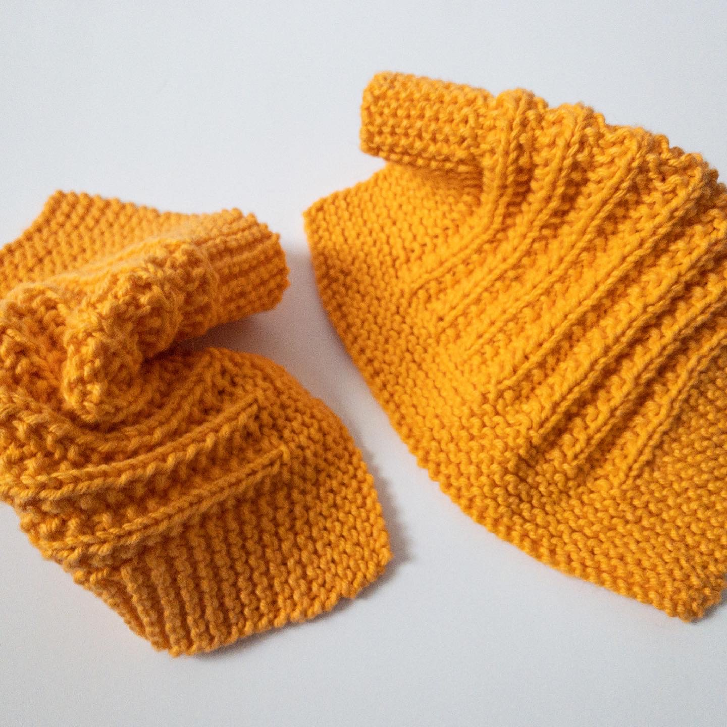 two square yellow-orange knitted cotton dishcloths