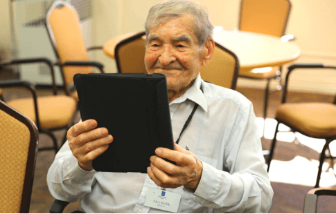 A senior enjoys a Televeda class from his tablet device