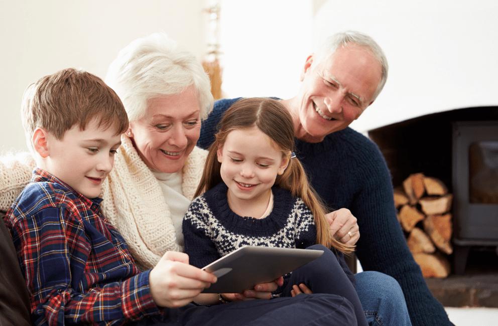 Senior couple and kids looking on ipad