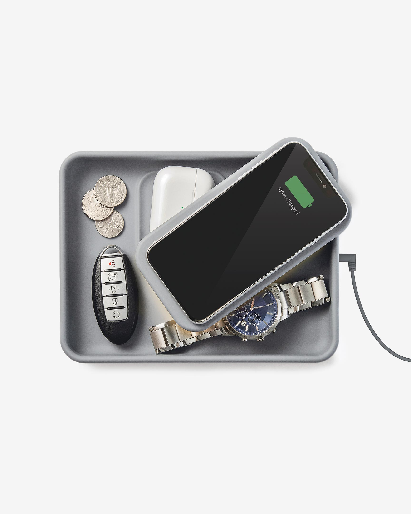 A phone and airpods are charging on top of the Tray Pivot. Key, coins, and a watch are inside the Tray Pivot