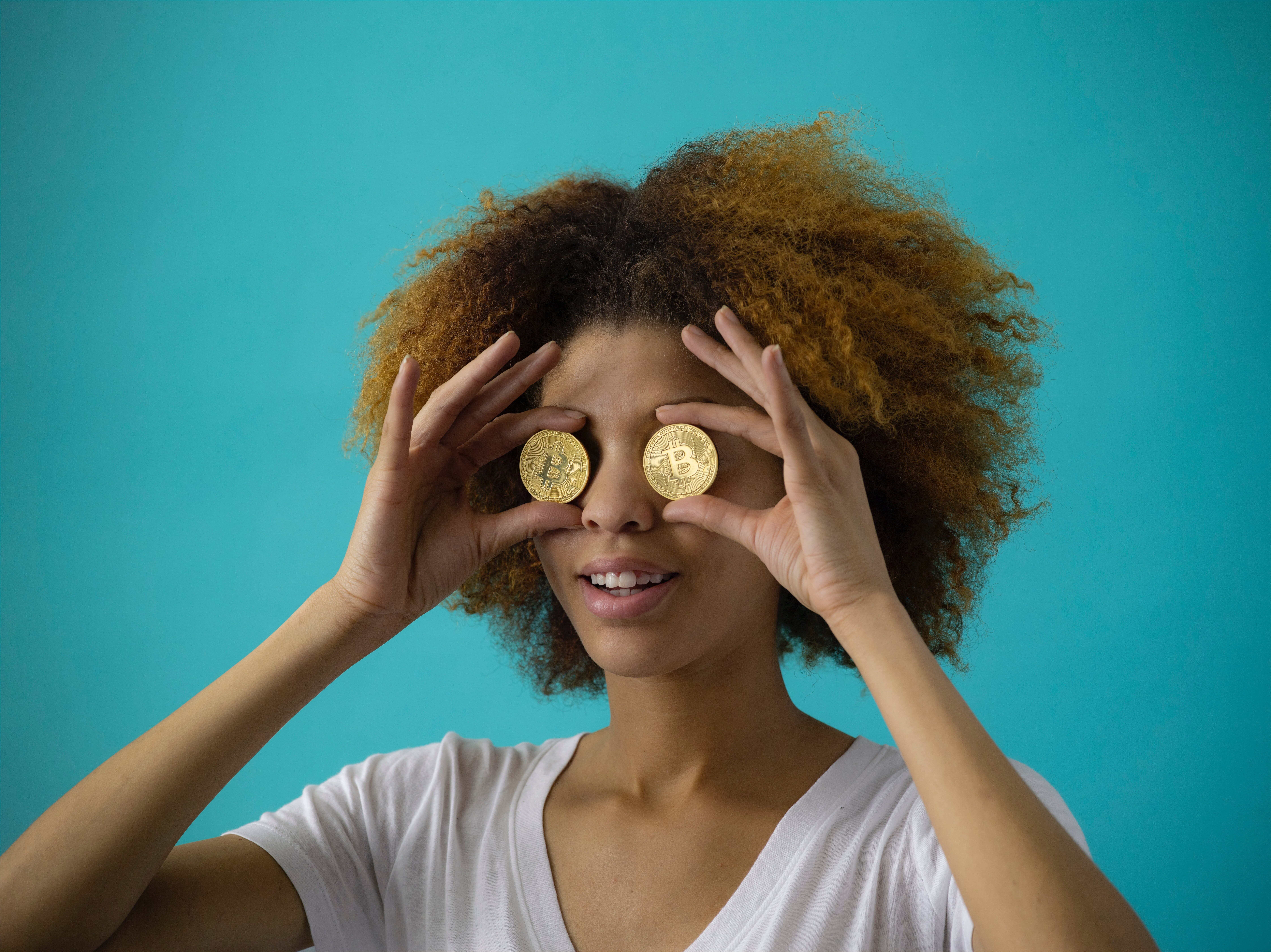 Photo of woman holding 2 Bitcoins in front of her eyes