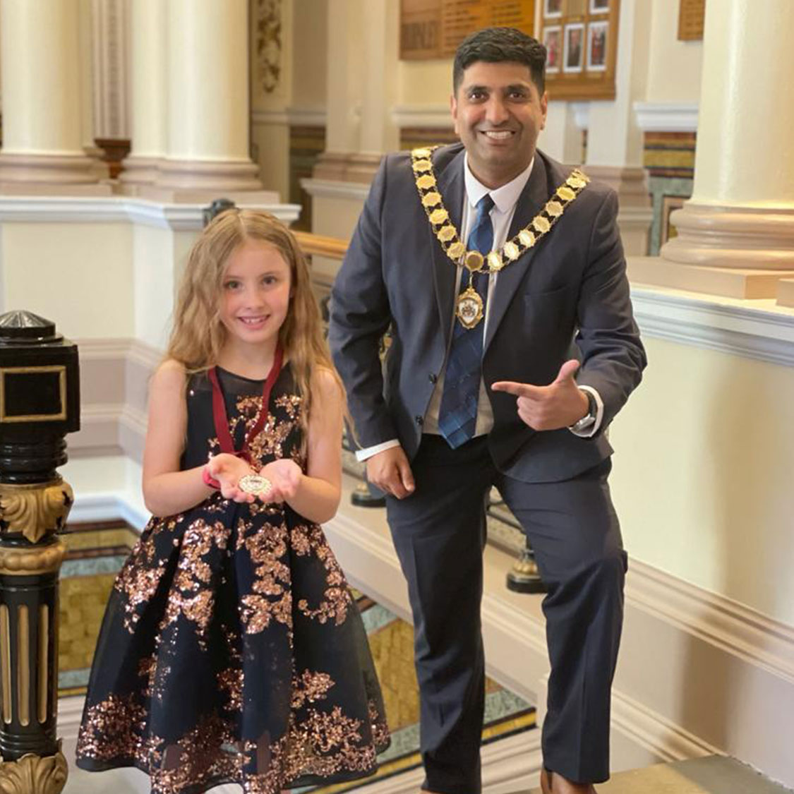 A photo of Annie stood next to the mayor holding her mayor's medal.