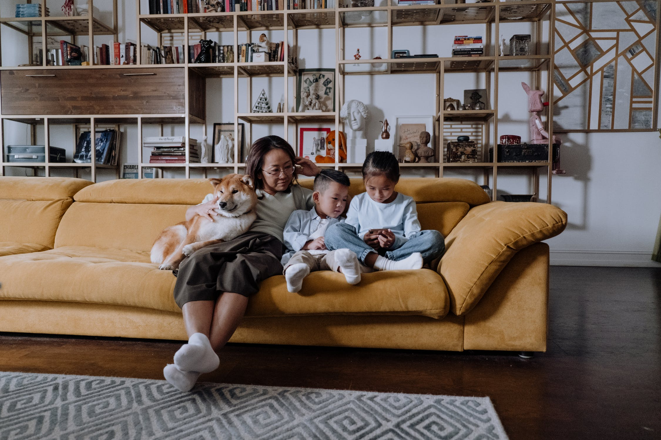 An image of a parent/guardian/grandparent watching two young children play a game on a smartphone on a large tan sofa in the living room.