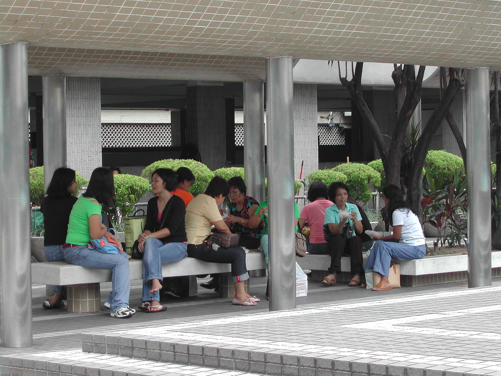 A group of female foreign domestic workers sitting on a bench in a sheltered area, chatting in small groups.