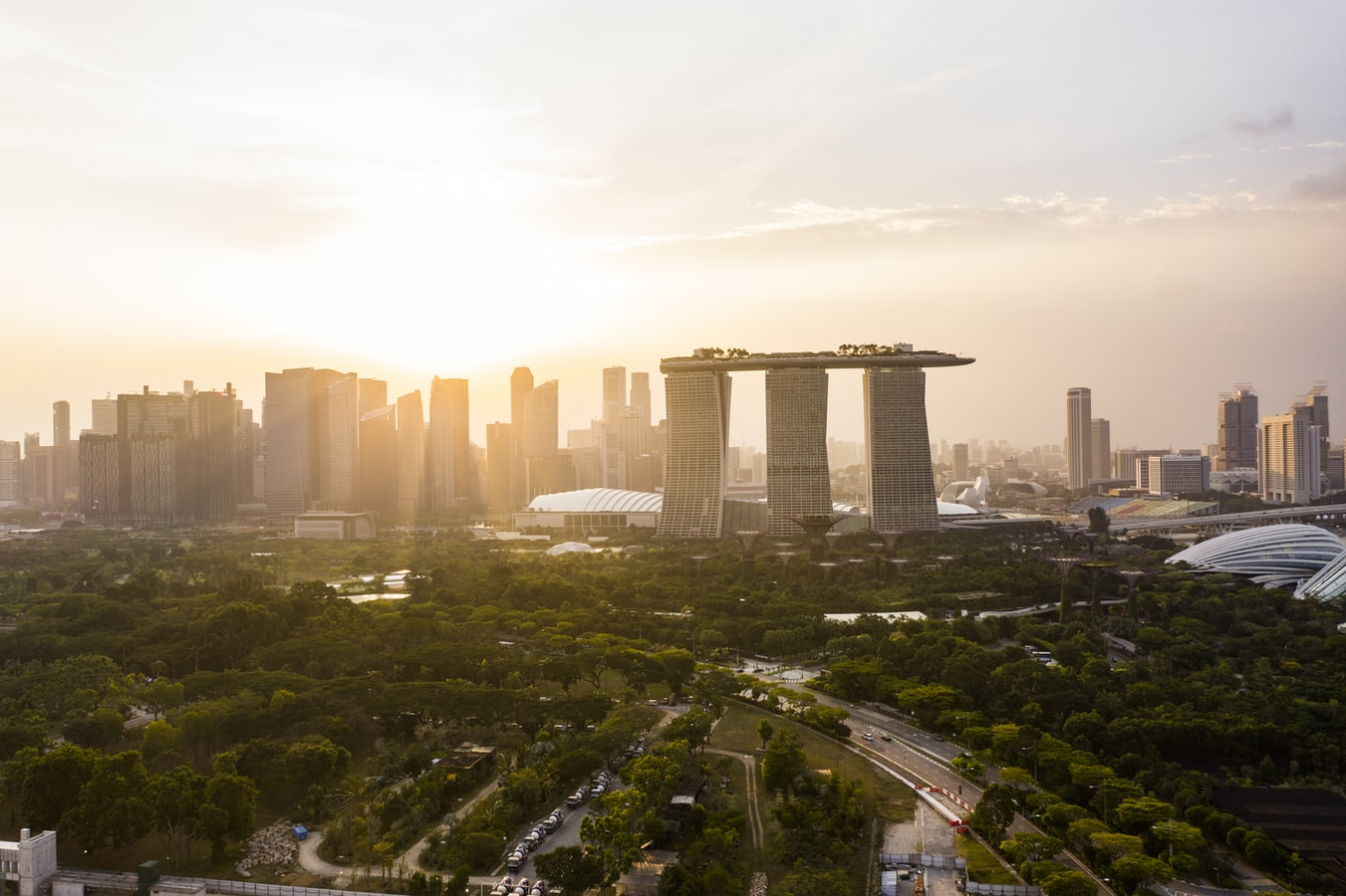 A bird's eye view of the Singapore city skyline in the evening, with Marina Bay Sands in clear view.