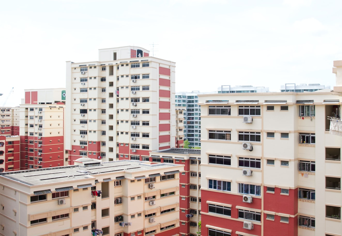 A view from a high level of a cluster of red and white HDB blocks of differing heights.