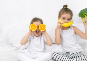two kids eating fruits