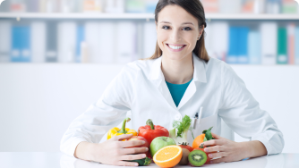 Woman smiling with a bowl of vegetables and fruits