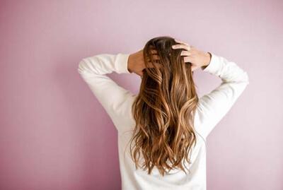 A woman having hair problems rubbing her hair