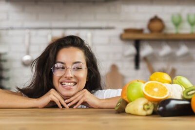 A woman smiling at some fruits and vegetables