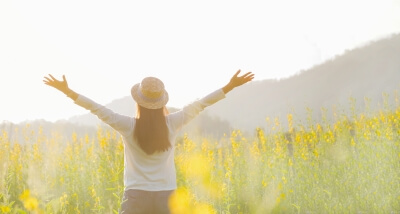 A girl looking at sunshine with her arms open in a green field