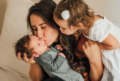 A mother showing love to her new born baby and her daughter