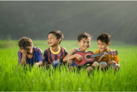Four kids laughing in a green field