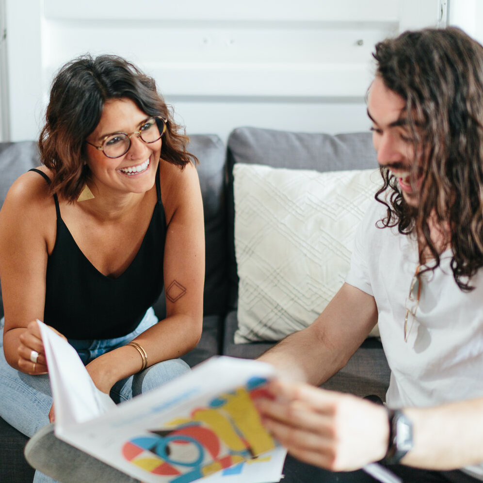Man and woman read a colorful Goodnewspaper on the couch while laughing and smiling
