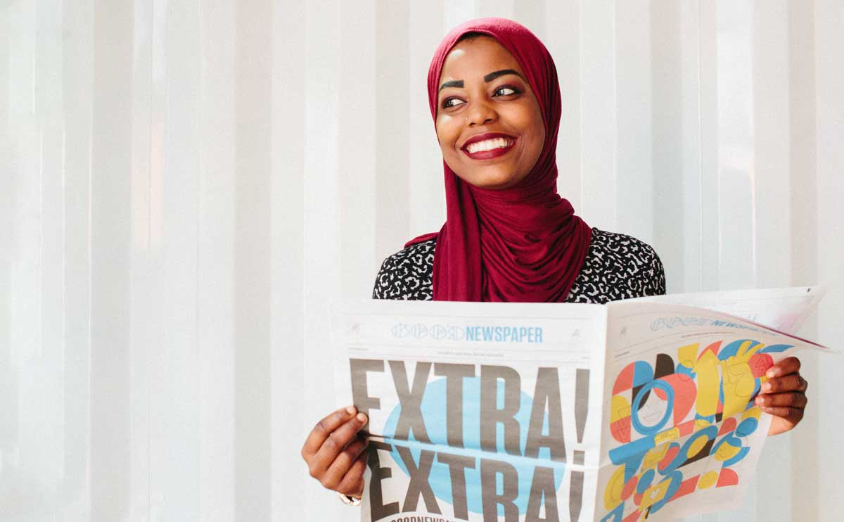 A smiling young woman wearing a hijab holds a colorful Goodnewspaper in a minimalist space