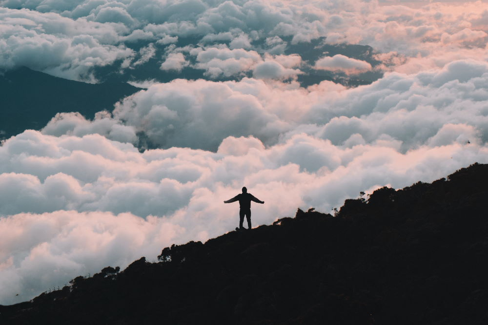 A man standing with arms outstretched, with beautiful clouds in the background