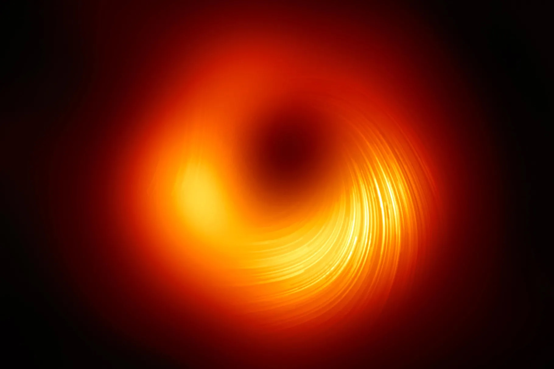 A Black Hole. Fiery orange and yellow light swirls around the black centre of a black hole.