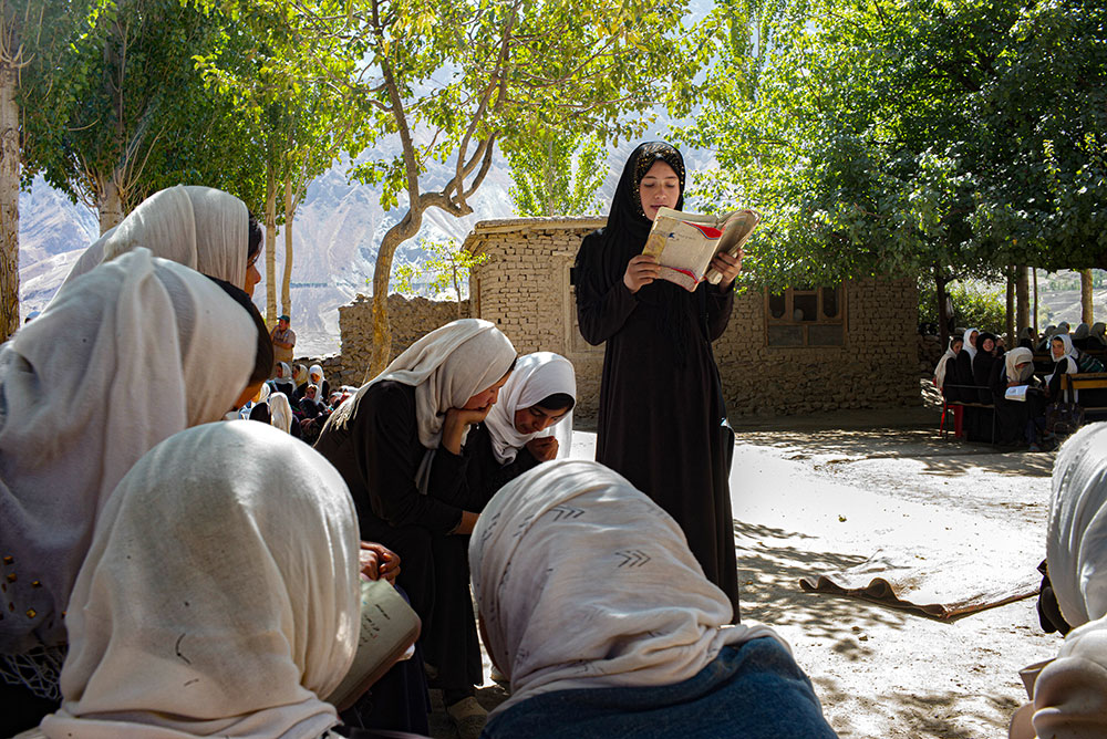 A women wearing black hijab and black clothes standing and reading a book in a group of sitting people
