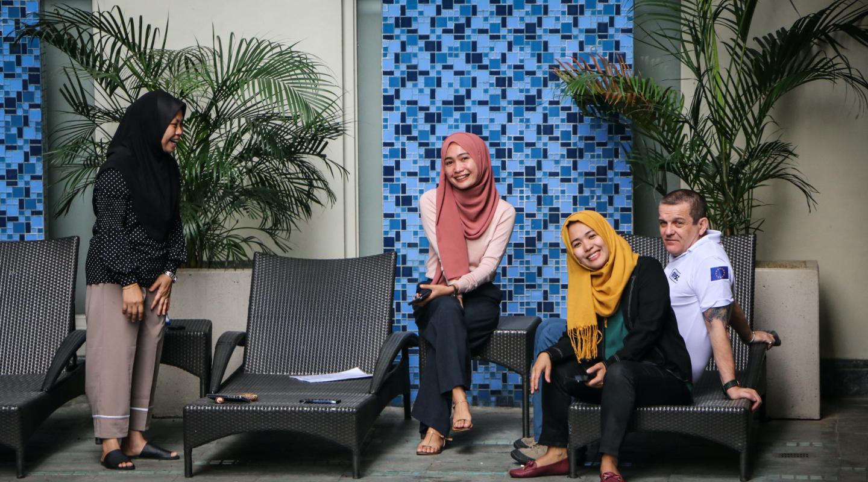 Three women wearing hijabs laughing and a man wearing T-shirt sitting